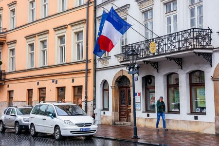 Krakow, poland - APR 30, 2019: France and EU flags on facade of Consulate General of the Republic of France in Krakow located in historic center of an old town. Citroen car on the wet street Editorial