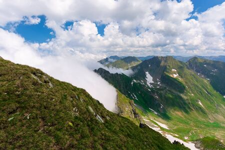 great summer scenery of high mountain range. steep slopes with rocks, grass and spots of snow. clouds on the blue sky. explore fagaras ridge of romania travel concept 免版税图像