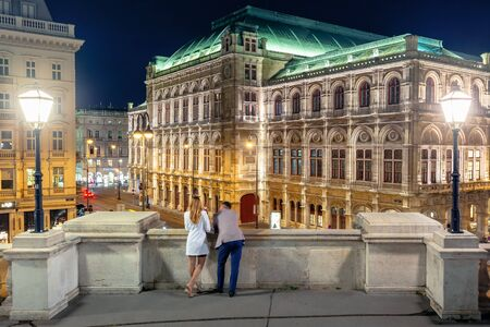 couple on the balcony of albertina enjoy the view. beautiful cityscape of vienna state opera house in austria at night. valentines day dating concept