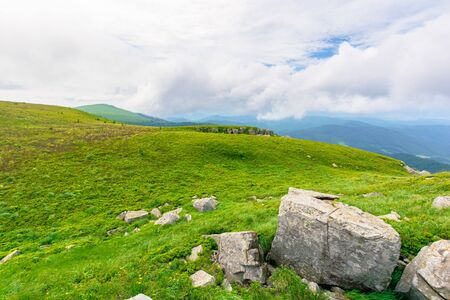 rock on the meadow. cloudy alpine summer. grass on the hills, slopes and humps of the mountain Reklamní fotografie