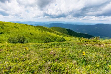 green meadows in mountains with clouds on the sky. wonderful summer nature landscape of carpathians. great travel scenery Stock Photo