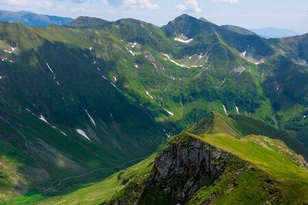 great summer scenery of high mountain range. steep slopes with rocks, grass and spots of snow. clouds on the blue sky. explore fagaras ridge of romania travel concept Stock Photo