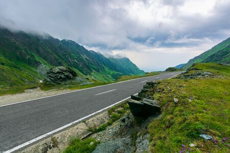 alpine road through mountain valley. epic view of transfagarasan route. popular travel destination. gorgeous landscape of fagaras mountains, romania. cloudy weather