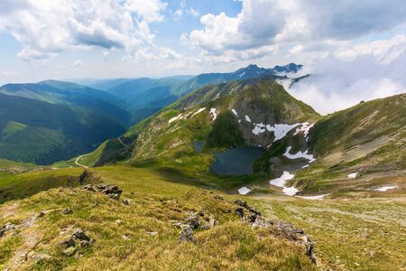 great summer scenery of high mountain range with alpine lake. steep slopes with rocks, grass and spots of snow. clouds on the blue sky. explore fagaras ridge of romania travel concept