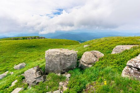 rock on the meadow. cloudy alpine summer. grass on the hills, slopes and humps of the mountain Stock Photo