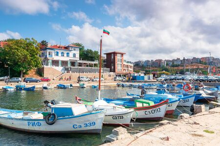 sozopol, bulgaria - SEP 09, 2019: fishing boats in port on a sunny day. town on the hill in the distance. bulgarian flag in the middle of a scene Stock Photo - 143991187