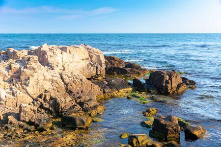 rocky sea coast in the morning. calm sunny weather Stock Photo