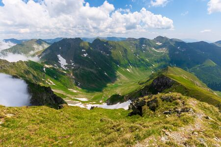 great summer scenery of high mountain range. steep slopes with rocks, grass and spots of snow. clouds on the blue sky. explore fagaras ridge of romania travel concept Reklamní fotografie