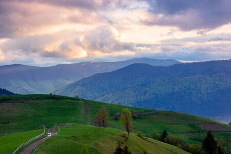 mountainous rural area. country road winding through agricultural fields on hills with forest. beautiful and vivid countryside landscape with cloudy sky at sunset