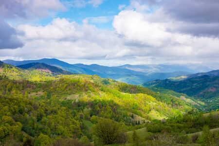 rural landscape in mountains. dappeled light on forested hills. beautiful nature scenery in spring. wonderful weather with clouds