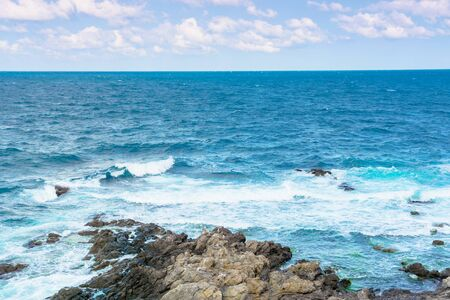 rocky sea shore in the afternoon. blue waves crashing the coast. fluffy clouds above the horizon. Stock Photo - 140833737