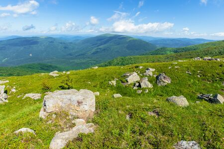 rocks on the alpine meadow. beautiful summer scenery of runa mountain. rural valley in the distance. sunny weather with fluffy clouds on the blue sky Stock Photo