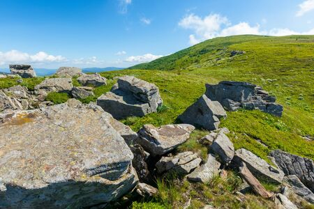 rocks on the alpine hillside meadow. beautiful summer nature scenery. green grass on the hills and fluffy clouds on the blue sky. stunning mountain landscape of carpathians Stock Photo - 141829176