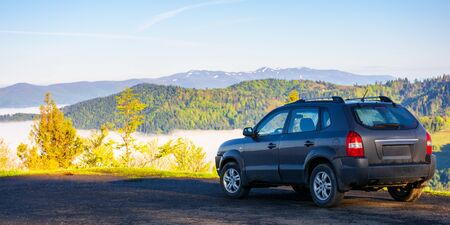 suv on the edge of a mountain. beautiful view in to the distant valley full of fog. ridge in the distance. fantastic springtime scenery in the morning. travel by car concept Stock Photo - 141829188