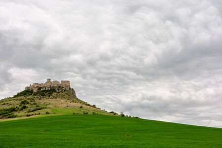 ruins of spis castle on a cloudy day in springtime. famous travel destination of slovakia.  grassy meadow at the foot of the hill.