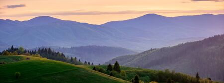 panorama of mountainous countryside in springtime at dusk. trees on the rolling hills. ridge in the distance. clouds on the sky. amazing rural landscape of carpathians