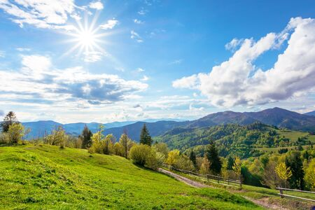 stunning rural landscape in mountains. country road through fields and meadows on hills rolling in to the distant ridge. nature scenery on a sunny day in spring. sun and fluffy clouds on the sky