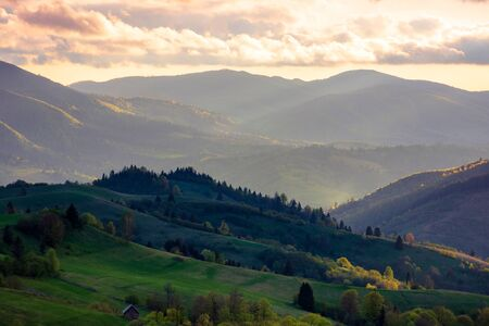 mountainous rural area. agricultural fields on hills with forest. beautiful and vivid countryside landscape with cloudy sky at sunset Stock Photo