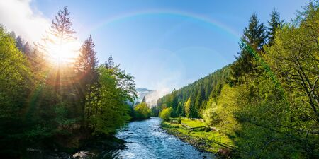 mountain river on a misty sunrise. fantastic nature scenery with fog rolling beneath a rainbow above the trees in fresh green foliage on the shore in the distance. beautiful countryside panorama Stock Photo