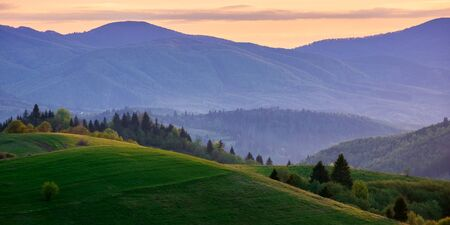 panoramic mountainous countryside in springtime at dusk. trees on the rolling hills. ridge in the distance. clouds on the sky. wonderful rural landscape of carpathians