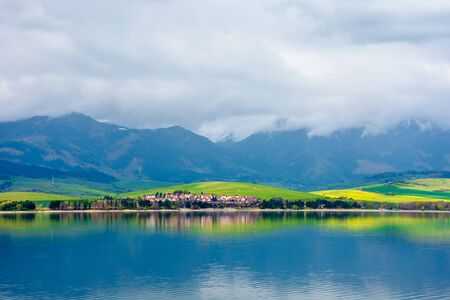 lake in mountains. cloudy day in springtime. beautiful scenery of high tatra mountains in dappled light. gorgeous landscape of liptovska mara, slovakia Stock Photo - 142707385