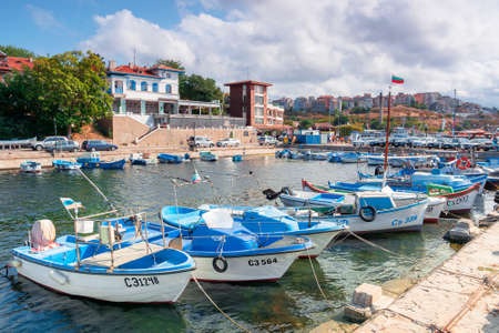 sozopol, bulgaria - SEP 09, 2019: fishing boats in port on a sunny day. town on the hill in the distance Stock Photo - 143991275