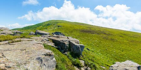 rocks on the alpine hillside meadow. beautiful summer nature scenery. green grass on the hills and fluffy clouds on the blue sky. wonderful mountain panorama of carpathians Stock Photo