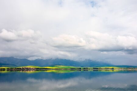 lake in mountains. cloudy day in springtime. great scenery of high tatra mountains in dappled light. beautiful landscape of liptovska mara, slovakia