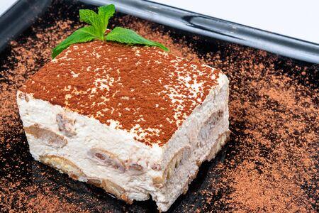tiramisu cake on a black plate. tasty italian dessert decorated with mint Stock Photo