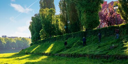 group of people scything the grass on a hump. lawn mowing in an old-school way on a sunny morning in springtime. location kyiv embankment in uzhgorod Stock Photo - 143244846
