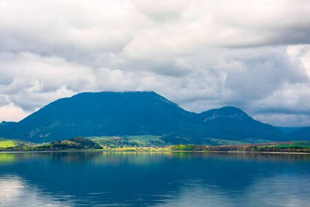 lake in mountains. cloudy day in springtime. beautiful scenery of high fatra mountains in dappled light. wonderful scenery of liptovska mara, slovakia Stock Photo