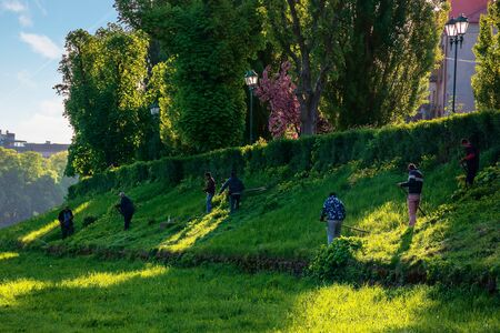 group of people scything the grass on a hump. lawn mowing in an old-school way on a sunny morning in springtime. location kyiv embankment in uzhgorod Stock Photo - 143439066