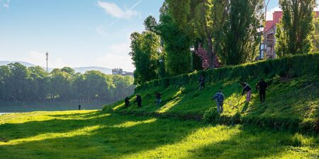group of people scything the grass on a hump. lawn mowing in an old-school way on a sunny morning in springtime. location kyiv embankment in uzhgorod Stock Photo - 143970305
