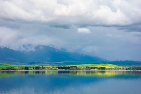 lake in mountains. cloudy day in springtime. great scenery of high tatra mountains in dappled light. beautiful landscape of liptovska mara, slovakia