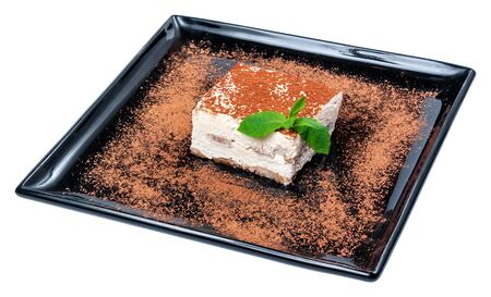 tiramisu cake on a black plate. tasty italian dessert decorated with mint Stock Photo