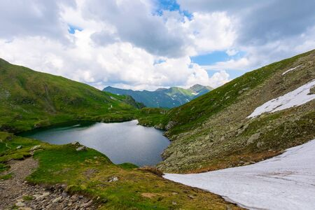 goat lake in the fagaras mountains of romania. popular travel destination. summer nature scenery with green grass and snow. ridge in the far distance beneath a cloudy sky