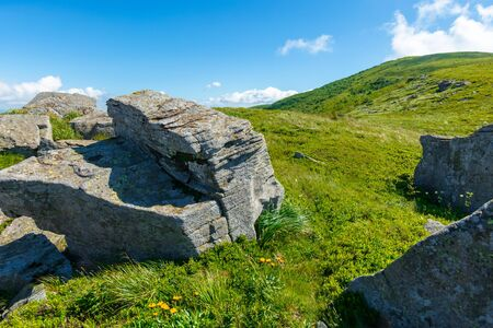 rocks on the alpine hillside meadow. beautiful summer nature landscape. green grass on the hills and fluffy clouds on the blue sky. wonderful mountain landscape of carpathians