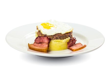 healthy homemade breakfast. fried egg and meat patty on top of smashed potato, decorated with bacon. food isolated on the white background. side view