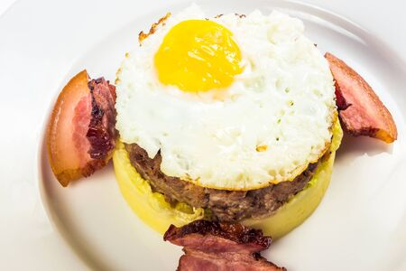 healthy homemade breakfast. fried egg and meat patty on top of smashed potato, decorated with bacon. food isolated on the white background. close up view