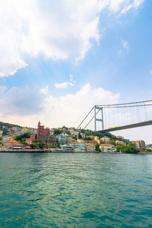 Fatih sultan mehmet bridge above the bosphorus. beautiful cityscape of historical area observed from the water on a sunny summer day. calm weather with fluffy clouds