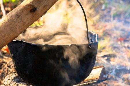 steaming old pot outdoor. cooking and camping. outdoor adventures concept. beaten cauldron on camp fire Stock Photo
