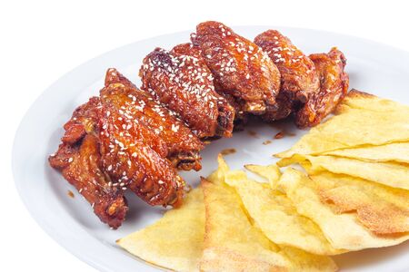 chicken wings in spicy sauce. popular pub dish. beautiful junk food concept. isolated on a white plate. Stock Photo