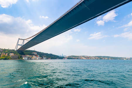 istanbul, turkey - AUG 18, 2015: fatih sultan mehmet bridge above the bosphorus. beautiful cityscape of historical area observed from the water on a sunny summer day. calm weather with fluffy clouds Editorial