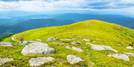 white rocks on the edge of alpine meadow. fresh green grassy slopes of mountain landscape in summer. distant ridges rolling in to the horizon. sunny weather with cloudy sky Stock Photo