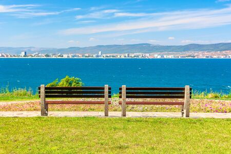 two benches on the sunny beach shore. beautiful skyline view from empty park with paved footpath on the seaside. city and mountain in the distance beneath a blue sky with clouds
