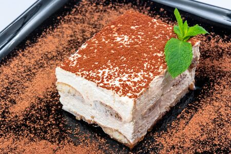 traditional rich tiramisu cake with cinnamon on a black plate. tasty italian dessert decorated with mint Stock Photo
