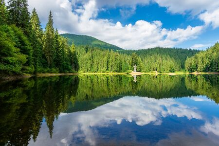reflection in the water. lake among the forest. beautiful nature landscape in summer. sunny weather with puffy clouds on the sky Stock Photo