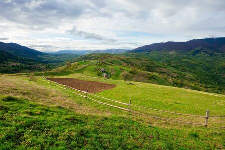 rural fields on mountain hills. beautiful rural landscape of carpathian nature on a cloudy day. path leads to village in the distance. fence across the grassy meadow Stock Photo