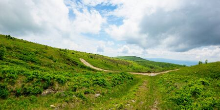 path through mountain landscape. road through green rolling hills. cloudy weather Stock Photo