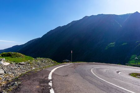 mountain road on a sunny morning. empty highway uphill through valley.  great european journey in summertime concept.